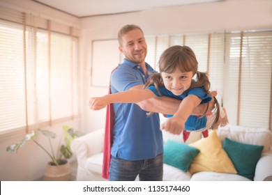 Young daddy and cute little girl in a superhero's costumes playing together at home on weekend. Superdad concept.