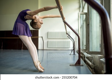 Young dancer doing a workout in the classroom near barre. Stretching back. Model rests in the hands of the barre.
