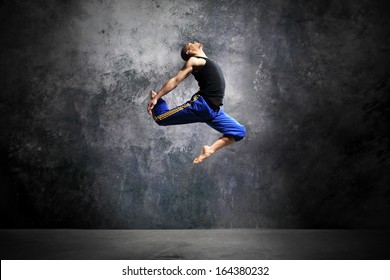 Young dancer is jumping on stage  /Modern urban dance