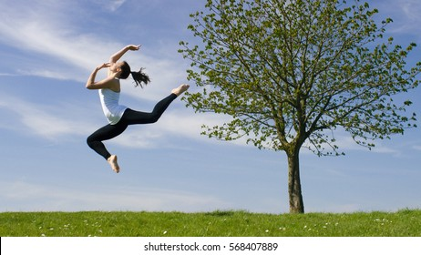 Young dancer jumps in the air outside