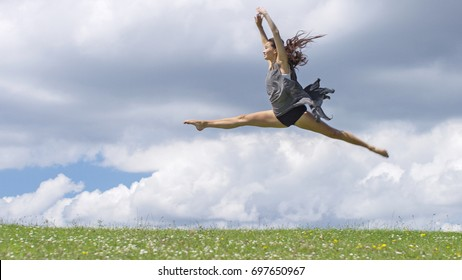 Young dancer in mid air doing the splits outdoors