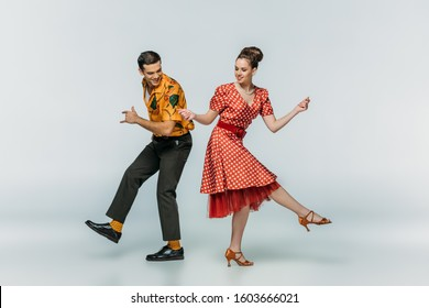 young dancers holding hands while dancing boogie-woogie on grey background