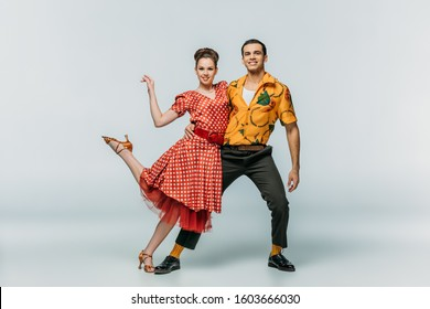 young dancers smiling at camera while dancing boogie-woogie on grey background