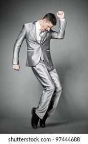 Young dancing businessman in elegant gray suit.