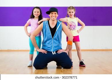 Young dancing teacher training children in modern zumba group choreography