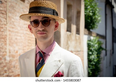 Young dandy wearing a tie, a red pocket handkerchief and a straw boater hat, taking a stroll in the streets of an Italian town