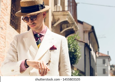 Young dandy wearing a tie, a red pocket handkerchief and a straw boater hat, checking the time in the streets of an Italian town