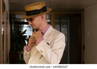 Young dandy wearing a tie, a red pocket handkerchief and a straw boater hat, adjusting his tie in front of a mirror