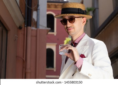 Young dandy wearing a tie, a red pocket handkerchief and a straw boater hat, having a drink in the streets of an Italian town