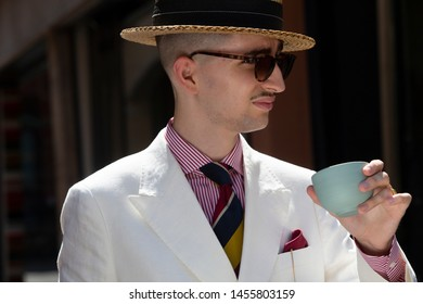 Young dandy wearing a tie, a red pocket handkerchief and a straw boater hat, having a coffee break in the streets of an Italian town