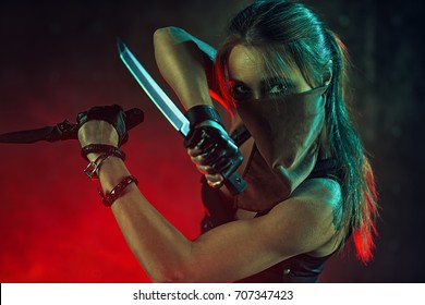 Young danger woman warrior with two knives portrait in dark night interior
