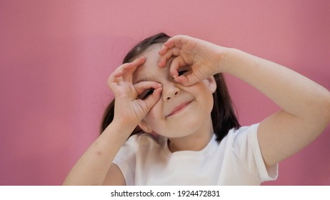 Young dark hair girl with funny ponytails makes glasses from fingers and smiles, looks at the camera. Pink background