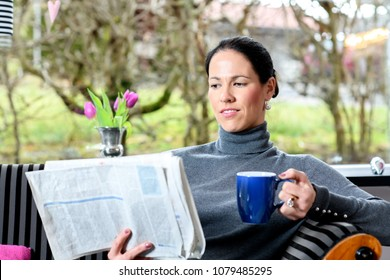 young dark haired woman at home with cup of coffeee relaxing and  reading newspaper