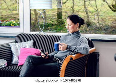 young dark haired woman at home with cup of coffeee relaxing
