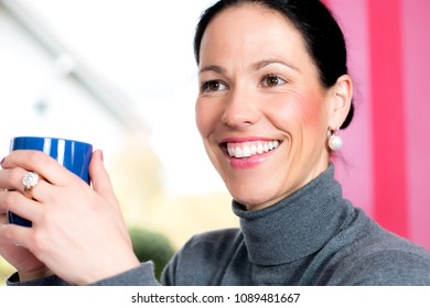young dark haired woman at home with cup of coffeee is smiling
