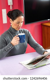 young dark haired woman at home with cup of coffeee reading newspaper