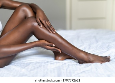 young dark skin woman with perfect body touching gently her hairless soft and silky legs after depilation in bed at home