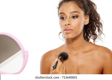 a young dark skinned woman applies a highlighter on her decolletage
