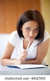 Young dark woman writing on notepad to do list at home