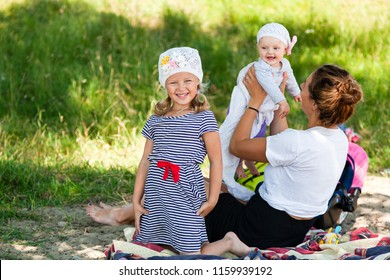 A young dark-haired female mom playing with her children: a five-year-old girl and a small baby sitting on a picnic in a green park on a summer day