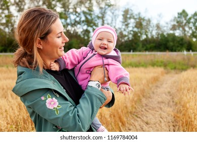 A young dark-haired female mom playing with her a small baby  on an autumn day against a background of a golden field and a  forest. Village Livestyle