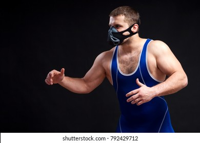 A young dark-haired man fighting  wrestling, grappling in a blue wrestling  clothes and trainig mask posing against a black isolated background