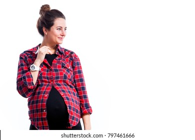 Young dark-haired pregnant woman in black dress and plaid shirt smiling and posing on isolated white background