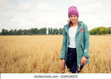 Young dark-haired woman in a knitted pink hat from a natural fur smiling and posing positively on an autumn day against a background of a golden field and a  forest. Village Livestyle