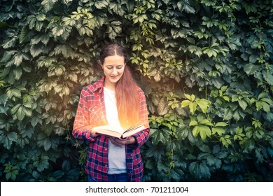 Young dark-haired woman in plaid red shirt and jeans holds in her hands and reads a magic book glowing with yellow lights against the beautiful green living wall of the grapes...