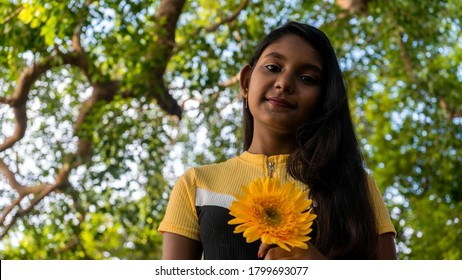 Young dark-skinned girl wearing a yellow top, holding a yellow gerbera flower at outdoor | low angle portrait with blurred trees in the background