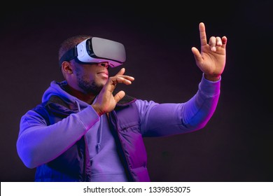 Young dark-skinned man dressed in outdoor wear having on head mobile virtual reality headset for playing 3D game but Mankind meets a new era of controlling real world objects from virtual reality.