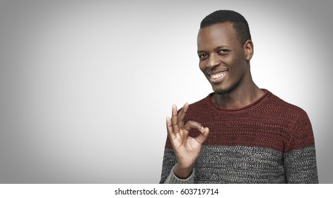 Young dark-skinned man having happy look, smiling, gesturing, showing OK sign. African American male showing OK-gesture with his fingers. Copy space for your advertising content. Body language concept
