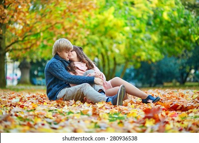 Young dating couple in Paris on a bright fall day sitting on the ground in autumn leaves