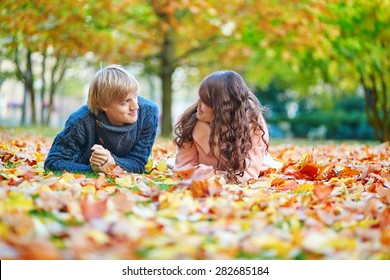 Young dating couple in Paris on a bright fall day lying on the ground in autumn leaves