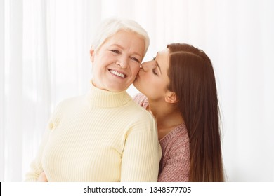 Young daughter kissing senior mother in cheek, having rest at home