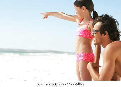 A young daughter points into the distance showing something to her father who is kneeling at her sideat beach