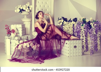 young daydream girl in dress with a train purple color sitting on luxury high chair flowers   background of the fashion interior and triangular pattern
