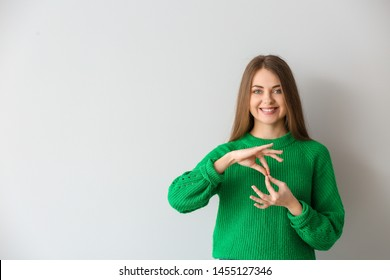Young deaf mute woman using sign language on light background