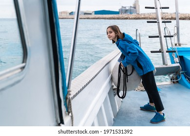 Young deckhand girl working inside vintage boat during summer vacation - Focus on face