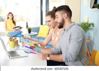 Young decorators sitting at desk in office