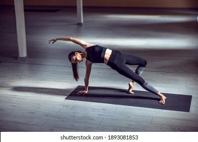 Young dedicated attractive slim yogi girl in Wild Thing yoga pose. Yoga studio interior.