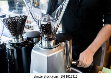 Young dedicated barista preparing coffee from fresh grinded roasted beans for a female customer in a modern coffee shop