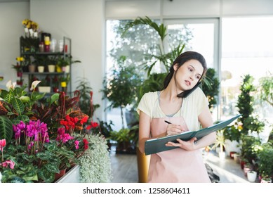 Young dedicated saleslady in floral shop  taking orders over the phone in garden center and holding a notebook