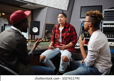 Young deejays taking interview with one of popular musician in their studio