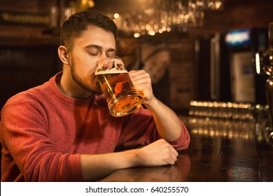 Young delighted man drinking beer with his eyes closed relaxing at the local pub copyspace leisure lifestyle activity recreation brewery restaurant beverage drink alcohol celebrating sipping pleasure