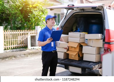 Young delivery man in blue uniform checking product boxes to send to customers on transportation vehicles.