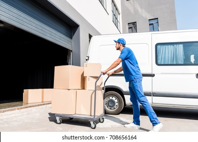young delivery man with cardboard boxes on cart driving into warehouse