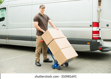 Young Delivery Man Holding Trolley With Cardboard Boxes