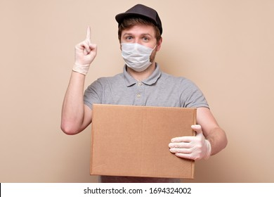 Young delivery man in medical mask holding a cardbox pointing up giving advice isolated on beige background