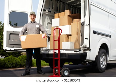 Young delivery man with parcel near cargo truck. Shipping service.